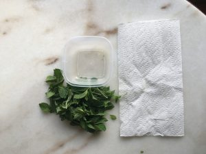 herb leaves with storage container and kitchen towel